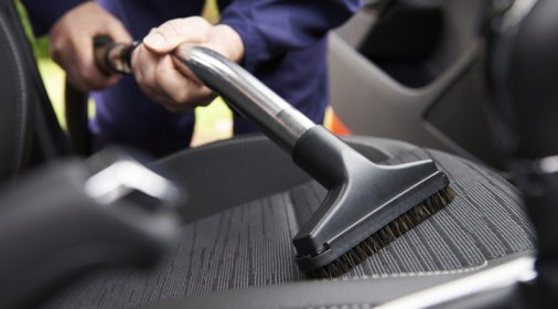 Man hoovering seat of a car during cleaning