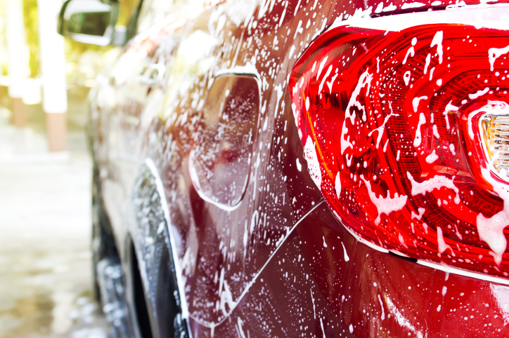a red car that is being washed with soap suds on it