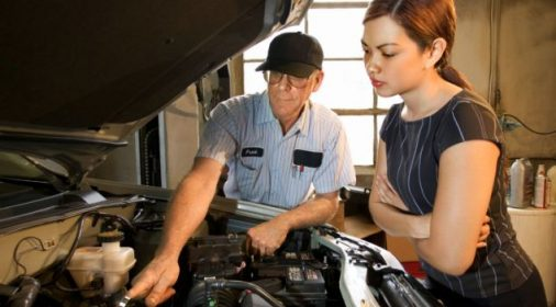 someone showing another person what is inside the car engine