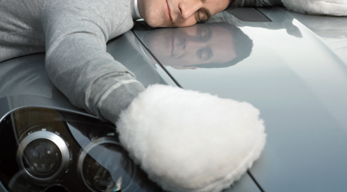 a person lying on their car