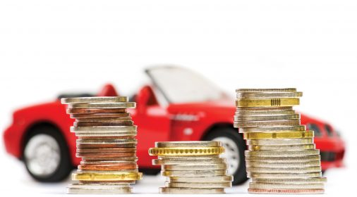 coins stacked up in front of a red toy car