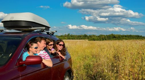 a family sat in a car leaning out of car window in a field