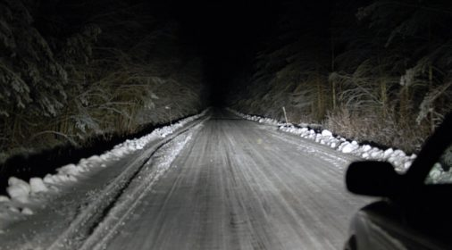 dark road with snow on it with trees either side, taken out of car window