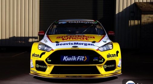 a yellow race car with kwik fit logo on the front of it