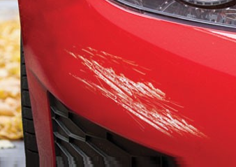 a red car with a scratch on the bumper