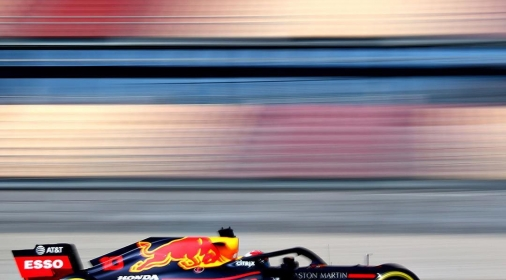 black and red race car on track with redbull logo, background blurred
