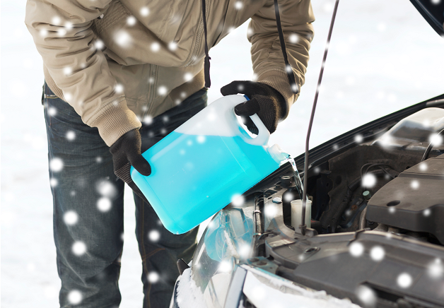 A man pouring antifreeze into a car