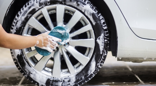 cleaning the cars alloy wheels with a blue cloth and soap.
