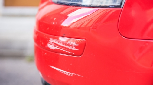 Red car bumper damage.