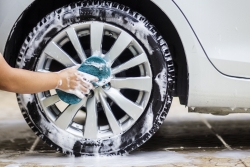 This image is a picture of wiping the car with a blue microfiber cloth by hands.Car wash concept. alloy wheel