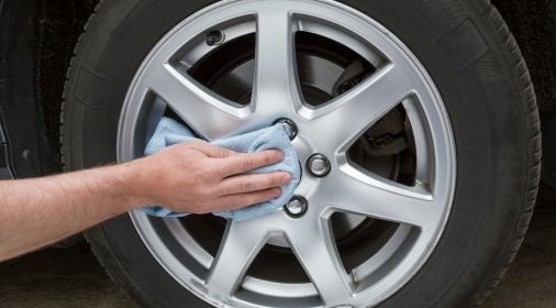 Man's hand with rag cleaning a dusty car wheel disk in the garage. Early spring washing or regular wash up. Professional car wash by hands.