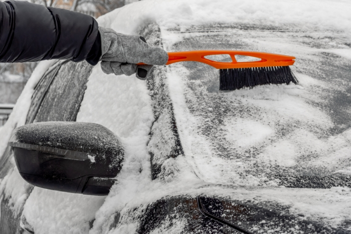 Man using Car Snow Brush to remove snow from the car windshield. Person in a black jacket and gray gloves. Close-up. Trees are covered with snow in the background. Winter, daytime.