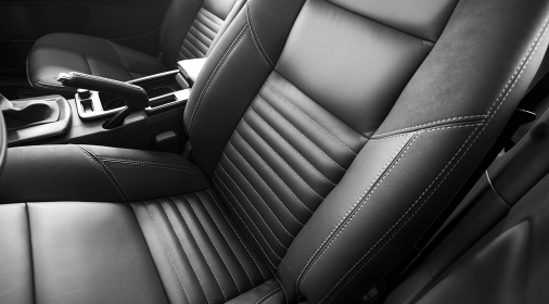 A black leather driver's and passenger's seat of a vehicle. The two seats are divided by a center console with the emergency brake visible. The driver's seat is positioned a bit further forward than the passenger's seat. The seats are stitched with white thread.