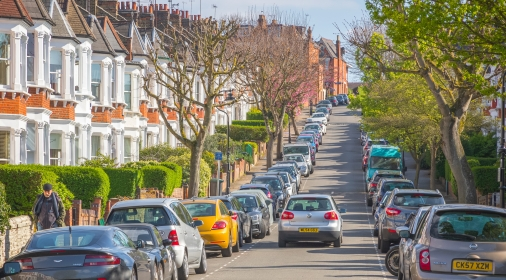 London, UK - 10 April, 2019 - A car driving through a London street lined with terraced houses and parked cars around Crouch End area