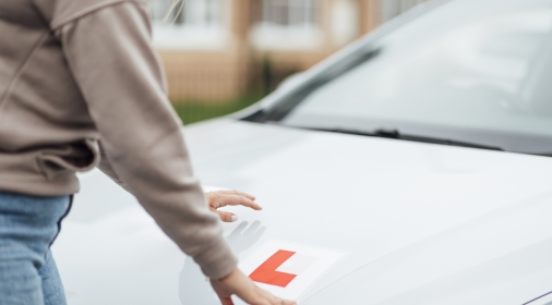 A shot of a Caucasian female putting L Plates on her car ready for her driving lesson.